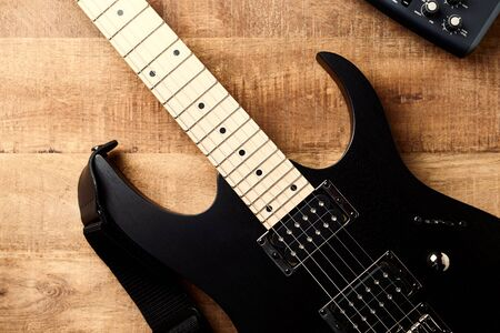 Body and fretboard of modern electric guitar on rustic wooden background. Top view. Copy space. Stock Photo - 129683872