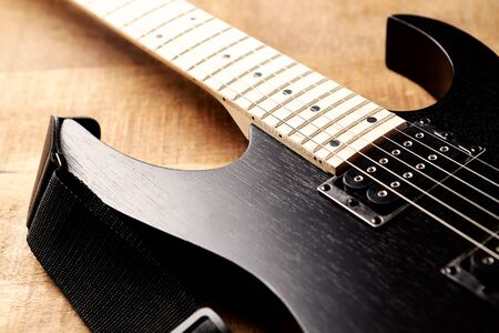 Body and fretboard of modern electric guitar on rustic wooden background. Stock Photo