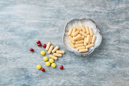 Vitamin C, Beta-Carotene tablets and Coenzyme Q10 capsules. Antioxidants. Concept for a healthy dietary supplementation. Rustic wooden background. Top view. Copy space.