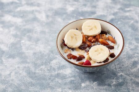 Bowl of granola with milk, nuts, raisins and banana. Concept for a tasty and healthy meal. Rustic wooden background. Copy space. Standard-Bild - 133185018