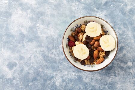 Bowl of granola with nuts, raisins and banana. Concept for a tasty and healthy meal. Rustic wooden background. Top view. Copy space. Standard-Bild - 133185211