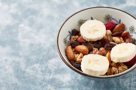 Bowl of granola with nuts, raisins and banana. Concept for a tasty and healthy meal. Rustic wooden background. Copy space. Standard-Bild - 133184613