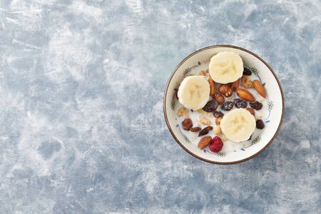 Bowl of granola with milk, nuts, raisins and banana. Concept for a tasty and healthy meal. Rustic wooden background. Top view. Copy space. Standard-Bild - 133186648