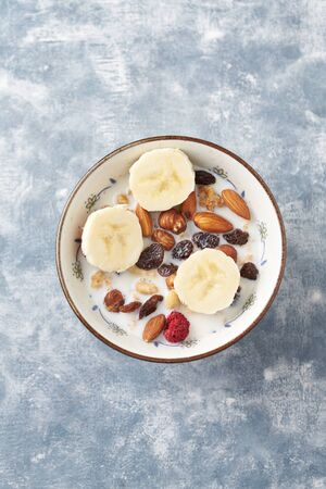 Bowl of granola with milk, nuts, raisins and banana. Concept for a tasty and healthy meal. Rustic wooden background. Top view. Copy space. Standard-Bild - 133186582