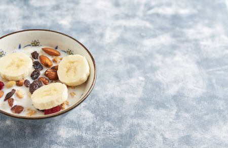 Bowl of granola with milk, nuts, raisins and banana. Concept for a tasty and healthy meal. Rustic wooden background. Copy space. Standard-Bild - 133184783