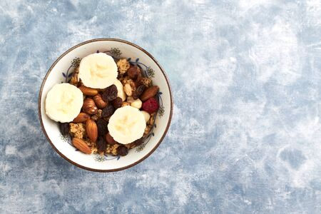 Bowl of granola with nuts, raisins and banana. Concept for a tasty and healthy meal. Rustic wooden background. Top view. Copy space. Standard-Bild - 133185759