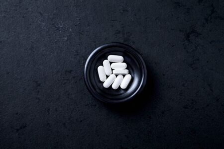 Lysine tablets. Concept for a healthy dietary supplementation. Nervous System Support. Black stone background. Top view. Copy space. Stock Photo