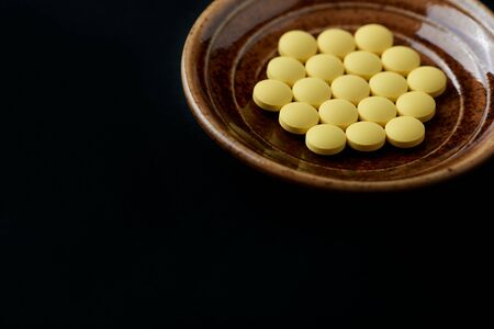 Vitamin C tablets on black paper background. Close up. Copy space.