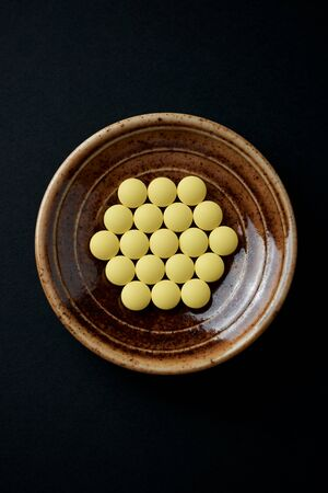 Vitamin C tablets on black paper background. Top view. Close up.