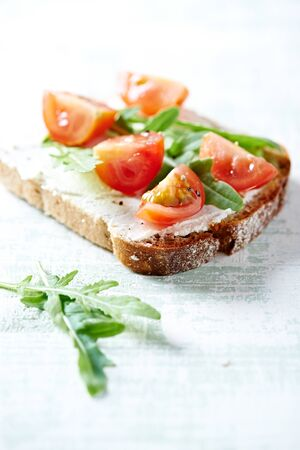 Tasty sandwiches with cream cheese, cherry tomatoes and fresh herbs. Bright wooden background. Close up.