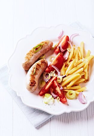 Grilled Sausages with french fries and tomatoes. White background.