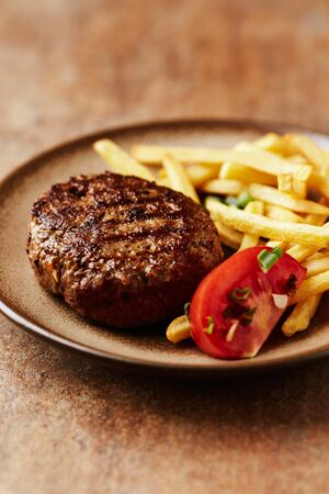 Fried hamburger steak with tomatoes and french fries. Rustic background. Close up.