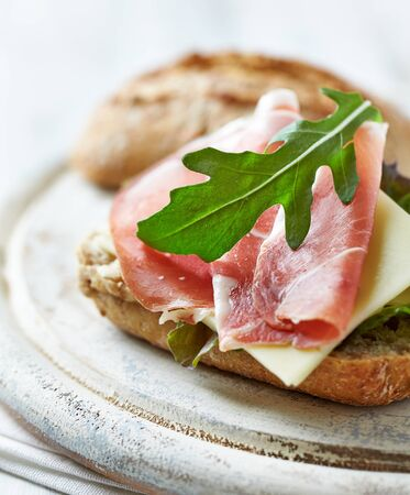 Sandwich with ham, cheese and lettuce. Bright wooden background.