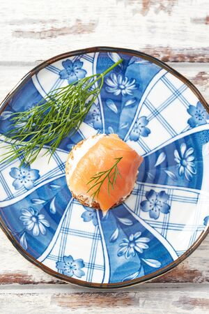 Smoked salmon canap? with cream cheese on bright wooden background.