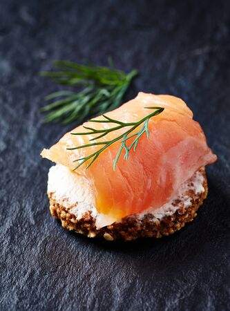 Smoked salmon canap? with cream cheese on black stone background. Close up. Banco de Imagens
