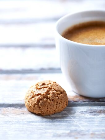Cup of coffee with amaretti (Italian biscuit) on white wooden background. Close up. Archivio Fotografico
