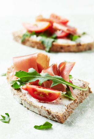 Tasty sandwiches with cream cheese, smoked ham and fresh herbs. Bright wooden background. Foto de archivo - 138176656