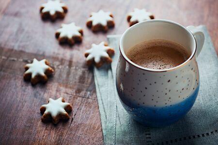 Mug of coffee and Christmas cookies (cinnamon stars) on rustic wooden background.