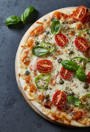 Pizza with mozzarella cheese, cherry tomatoes, jalapeno pepper, capers and fresh basil. Top view.