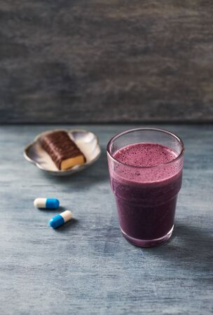 Glass of Protein Shake with milk and blueberries, Creatine capsules and Protein bar. Concept for Sport nutrition. Rustic wooden background. Copy space.