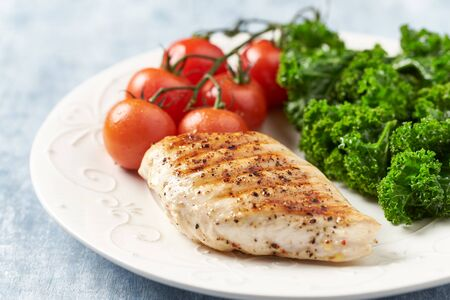 Grilled Chicken Breast with roasted Cherry Tomatoes. Bright wooden background