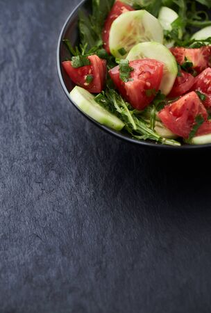 Salad with Tomatoes, Cucumber and Rocket on stone Background. Healthy Snack Idea. Copy space.