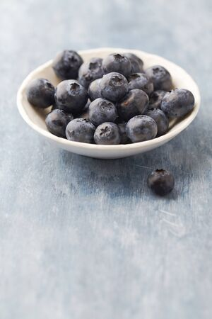 Bilberries on bright wooden background. Concept for healthy nutrition. Copy space.