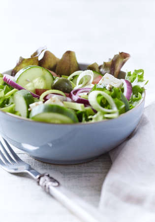 Salad with Green Olives, Cucumber and Feta Cheese. Bright wooden background.