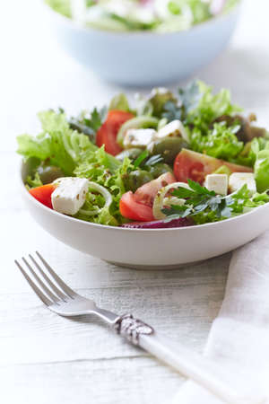 Salad with Green Olives, Tomatoes and Feta Cheese. Bright wooden background.