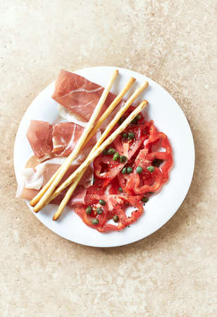 Plate of smoked ham with tomatoes, capers and grissini. Stone background. Top view.