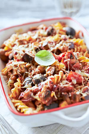 Baked fusilli pasta with cherry tomatoes, olives and mozzarella cheese. Bright wooden background. Close up.