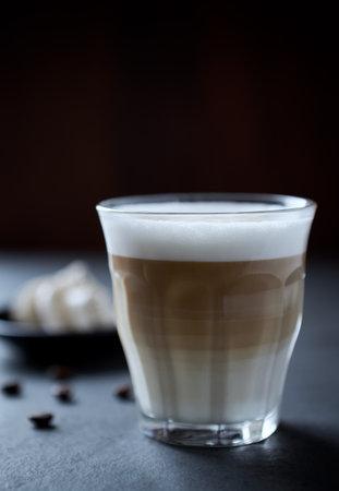 Coffee with milk on dark stone background. Close up.