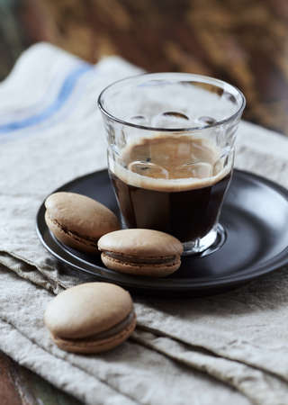 Coffee in glass cup on rustic wooden background. Close up.