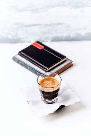 Coffee in glass cup on bright wooden background.