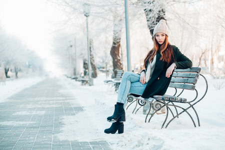 woman in winter park sitting on the bench Фото со стока - 37174303
