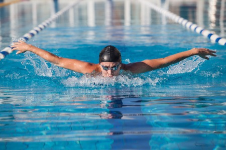 front raise: dynamic swimmer in cap glasses in the pool