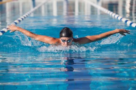 profesionistas: nadador dinámico en vasos de cabeza en la piscina