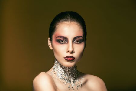 portrait of beautiful girl with beautiful makeup and silver on the neck. cosmetics photo