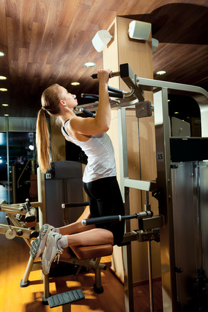 ups: Woman working out in gym - pull ups.