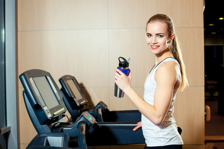 girl working out: Pretty girl working out in a treadmill at the gym and smiling.
