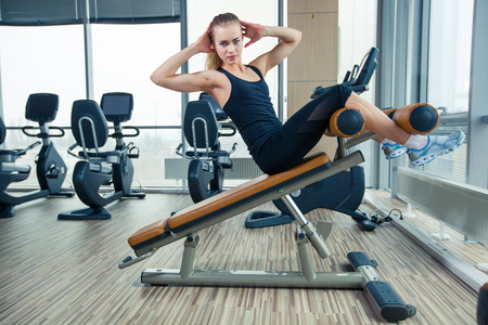 Beautiful sport woman doing press fitness exercise at sport photo