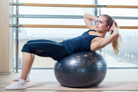 girl working out: Young girl working out at the gym with a ball.
