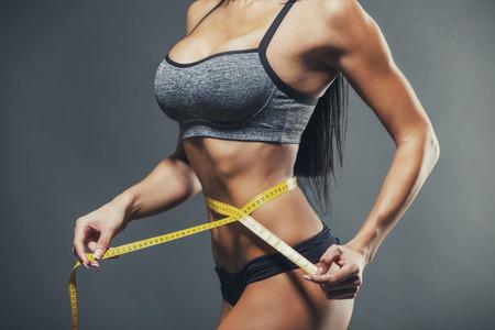 cinta metrica: Mujer que mide su cintura con una cinta métrica amarilla.