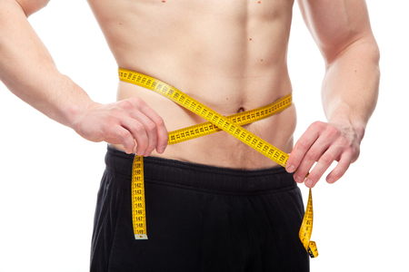loss weight: Fit man measuring his waist after a workout in the gym, isolated in a white background.