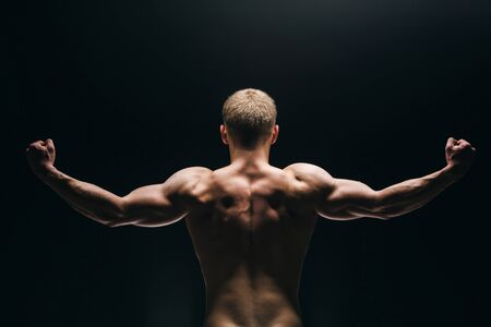 naked african: Close up of sports mans muscular back isolated on black background