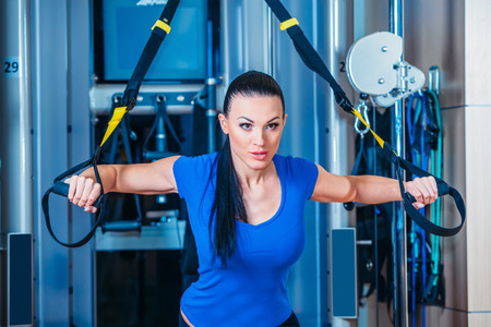 personal training: Young attractive woman training with htrx fitness straps in the gyms studio Stock Photo