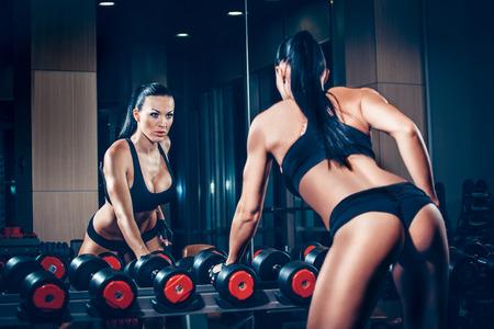 sudoracion: Chica sexy joven descansando después de ejercicios de pesas. Fitness mujer descansando en el gimnasio. Foto de archivo