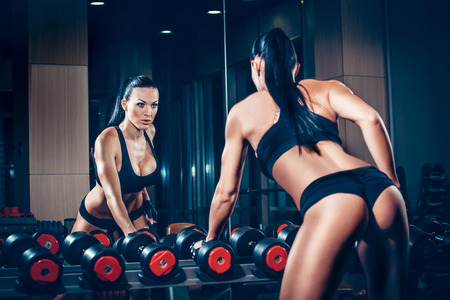 muscle toning: sexy young girl resting after dumbbells exercises. Fitness woman  resting in gym.