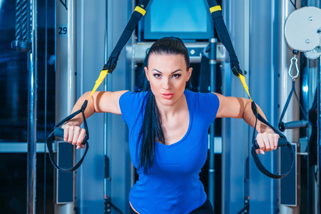 woman stairs: fitness, sports, exercise, technology and people concepts - smiling young woman doing exercise at the gym Stock Photo