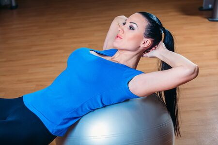 fitness, sports, training, lifestyle - smiling woman with implementation of exercises on the ball in gym.